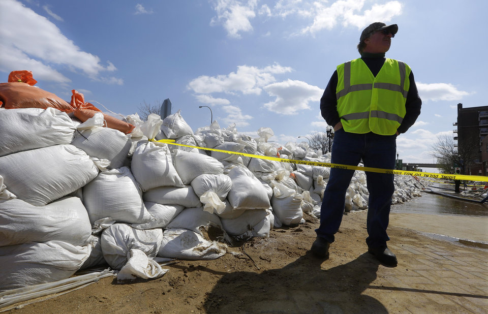 Peoria Maintenance Engineer Jim Clark monitors the sand bag wall holding back the Illinois River from recent flooding Wednesday, April 24, 2013, in Peoria, Ill. The Illinois River finally crested Tuesday at 29.35 feet, eclipsing a 70-year record in Peoria. (AP Photo/Seth Perlman)