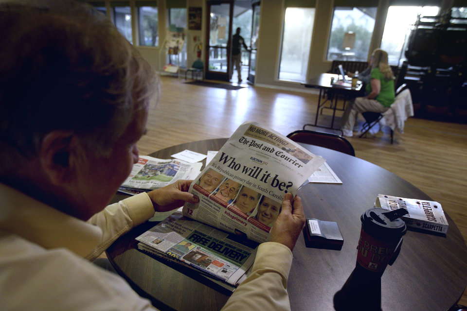 Photo - Poll manager Michael Blalock reads a newspaper as he waits for voters at his polling site Saturday, Jan. 21, 2012, in Sullivan's Island, S.C. (AP Photo/David Goldman) ORG XMIT: SCDG104