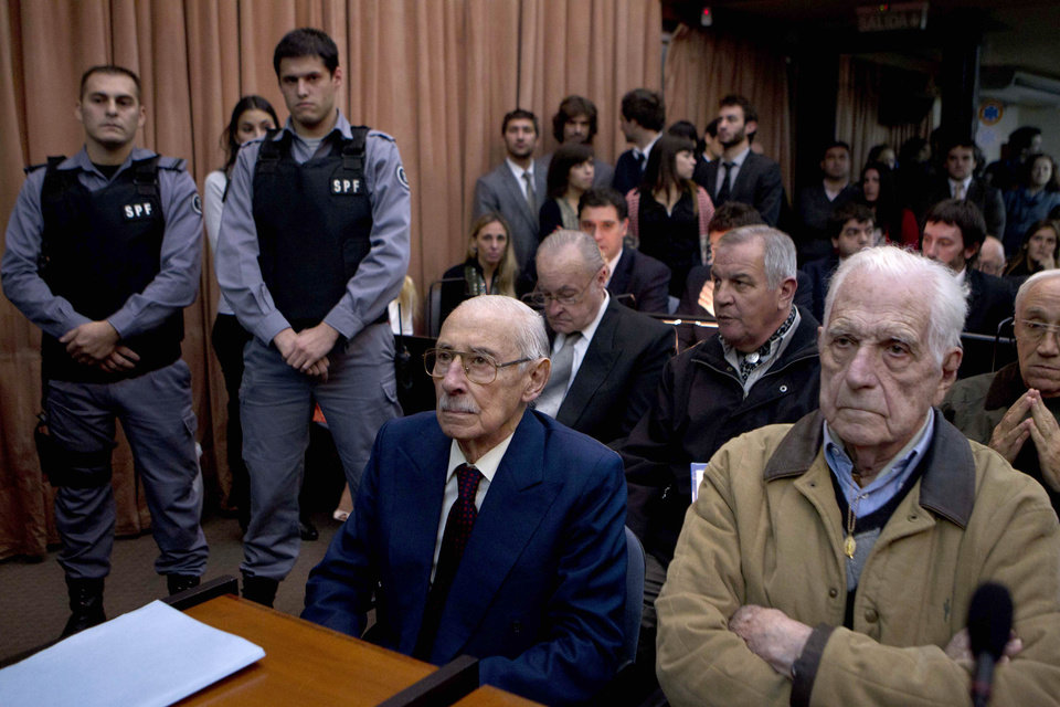 Photo -   Former dictators Jorge Rafael Videla, second from right, and Reynaldo Bignone, right, wait to listen the verdict of Argentina's historic stolen babies trial in Buenos Aires, Argentina, Thursday, July 5, 2012. The two former dictators and a handful of other retired military and police officials are accused of systematically stealing babies from leftists who were kidnapped and killed when a military junta ran the country three decades ago. (AP Photo/Natacha Pisarenko)