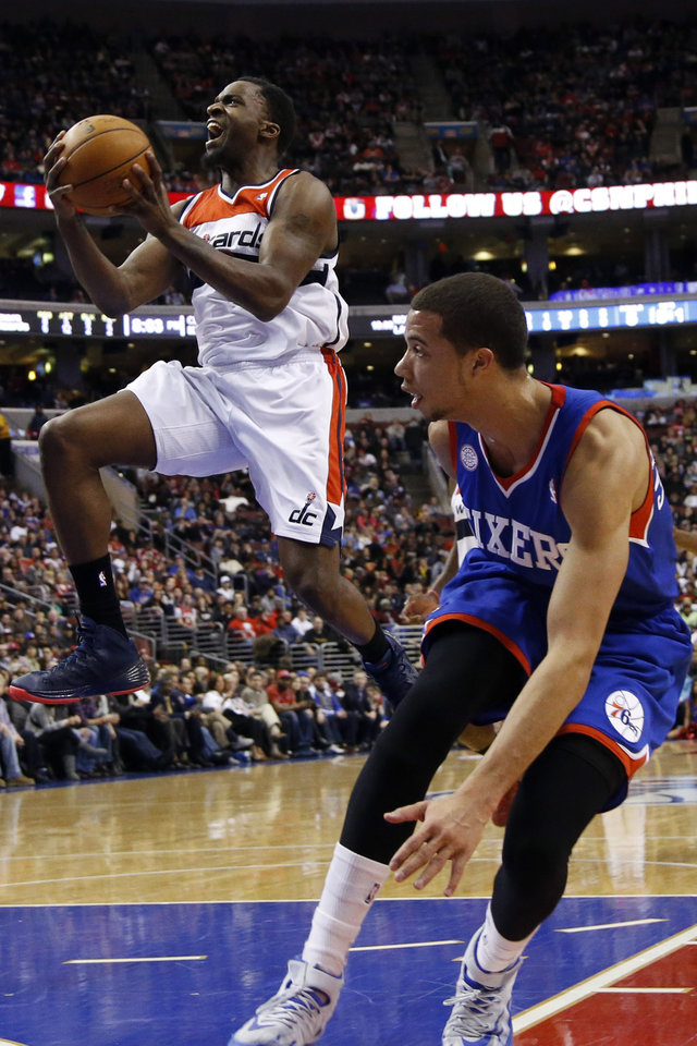 Photo - Washington Wizards' Martell Webster, left, goes up for a shot as Philadelphia 76ers' Michael Carter-Williams looks on during the first half of an NBA basketball game, Saturday, March 1, 2014, in Philadelphia. (AP Photo/Matt Slocum)