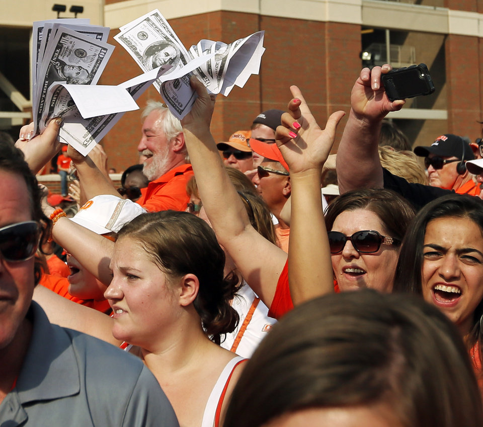 Photo - OSU fans hold up fake money during the Spirit Walk before a college football game between the Oklahoma State University Cowboys (OSU) and the Lamar University Cardinals at Boone Pickens Stadium in Stillwater, Okla., Saturday, Sept. 14, 2013. Sports Illustrated's investigation of the OSU football team alleged players had received money while shaking hands with boosters during Spirit Walks in the past. Photo by Nate Billings, The Oklahoman