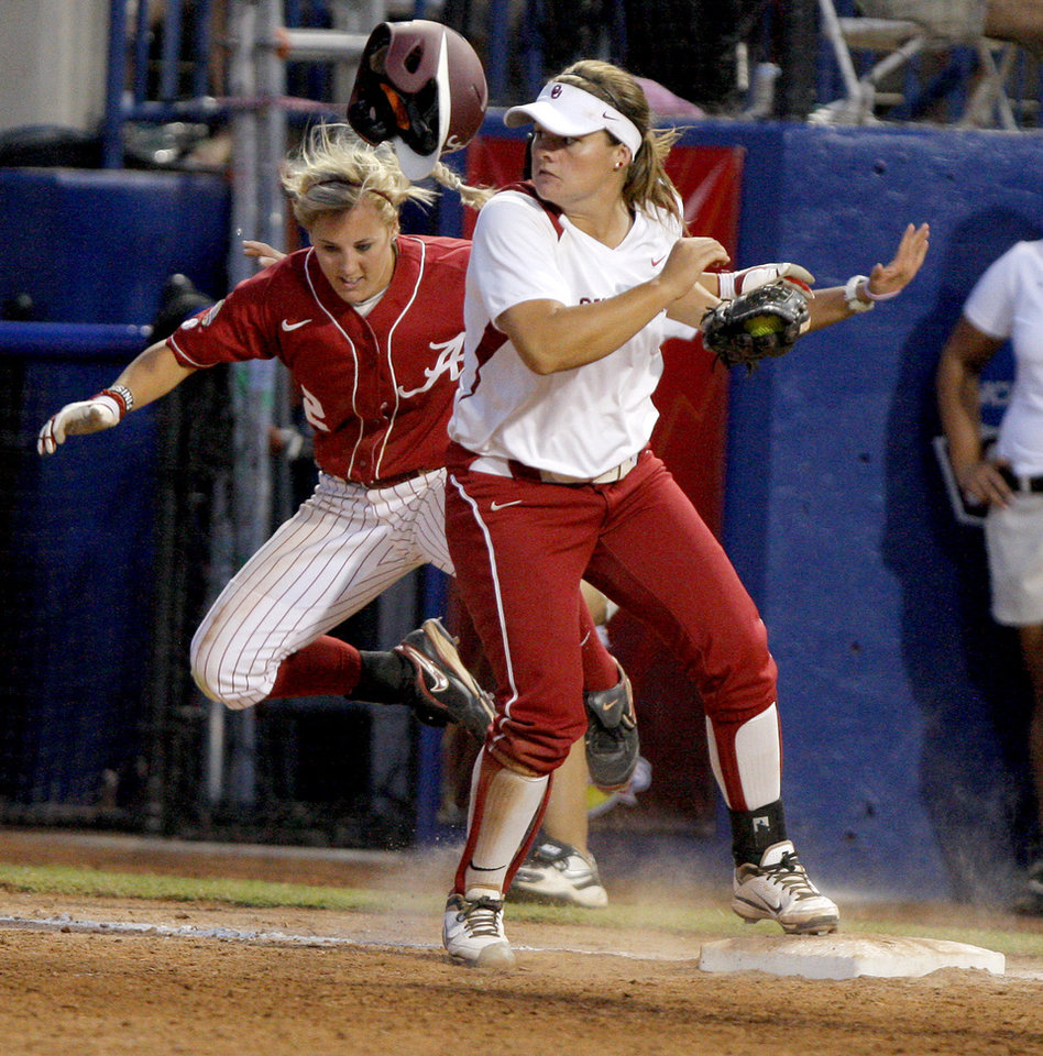 Photo - Alabama's Jazlyn Lunceford (2) falls down behind Oklahoma's Georgia Casey (42) after she was called out at first in the fifth inning during the championship game of the Women's College World Series as ASA Stadium in Oklahoma City, Tuesday, June 5, 2012. Photo by Bryan Terry, The Oklahoman