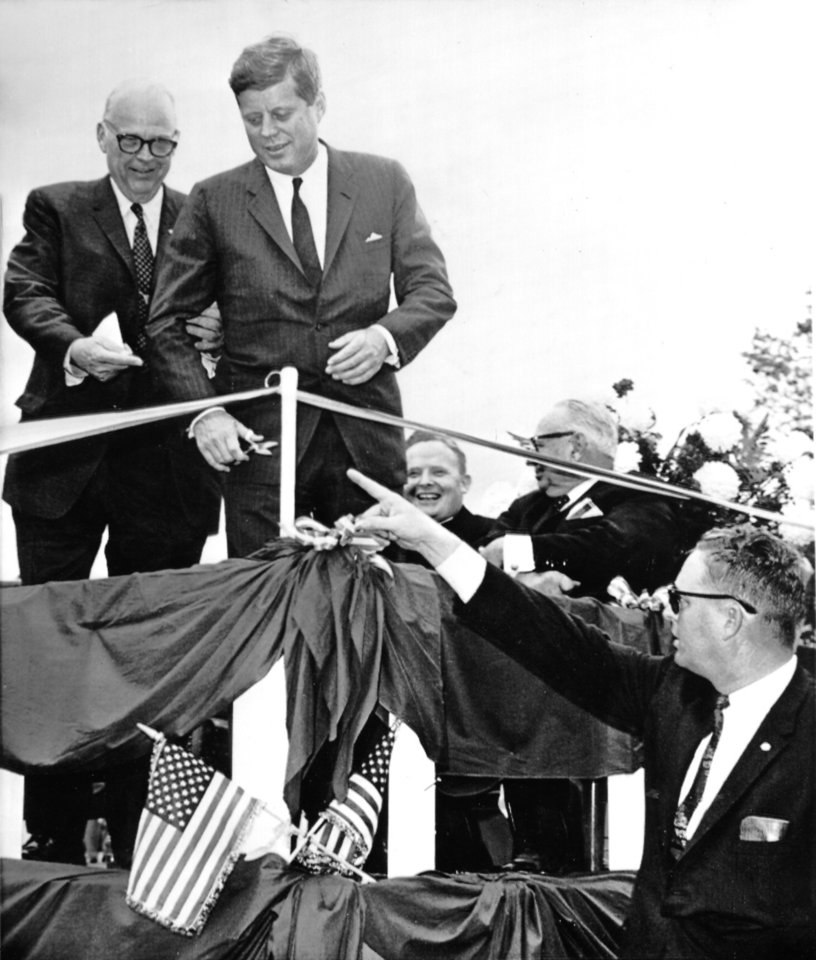 Photo - Sen. Robert S. Kerr shows President John F. Kennedy where to cut the ribbon, officially opening State Highway 103 at Big Cedar.  The man on the ground, also directing the president, is unidentified. AP Photo