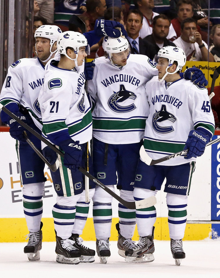 Photo - Vancouver Canucks' Chris Tanev (8) celebrates his goal against the Phoenix Coyotes with teammates Mason Raymond (21), Cam Barker (18) and Jordan Schroeder (45) during the first period of an NHL hockey game on Thursday, March 21, 2013, in Glendale, Ariz. (AP Photo/Ross D. Franklin)