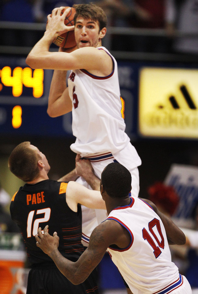 Kansas center Jeff Withey (5) rebounds over Oklahoma State guard Keiton Page (12) and passes to guard Tyshawn Taylor (10) during the first half of an NCAA college basketball game in Lawrence, Kan., Saturday, Feb. 11, 2012. (AP Photo/Orlin Wagner) <strong>Orlin Wagner</strong>