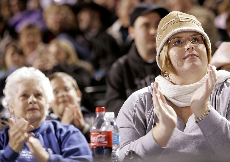 Photo - Carrie Knightley, of Oklahoma City (right) and Eleanor Fuller, (left) of Yukon, clap as they watch the Centennial Spectacular on the outfield monitor at the AT&T Bricktown Ballpark in Oklahoma City as part of the State's Centennial celebration. By John Clanton, The Oklahoman