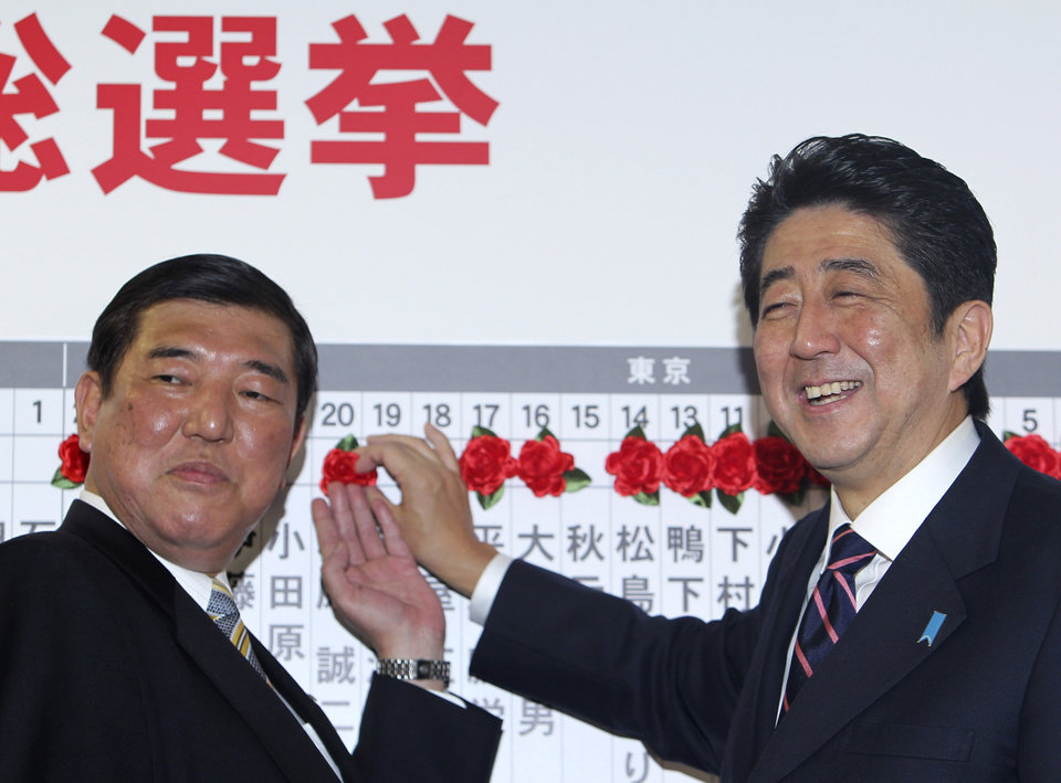 Japan\'s main opposition leader Shinzo Abe, right, of the Liberal Democratic Party, and the party Secretary-General Shigeru Ishiba pose for photos as they place a rosette on the name of one of those elected in parliamentary elections at the party headquarters in Tokyo Sunday, Dec. 16, 2012. Japan\'s conservative LDP stormed back to power Sunday after three years in opposition, exit polls showed, signaling a rightward shift in the government that could further heighten tensions with rival China. (AP Photo/Junji Kurokawa)