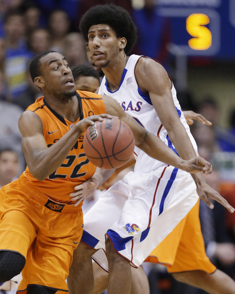 Photo - Oklahoma State guard Markel Brown (22) is fouled by Kansas forward Kevin Young (40) during the first half of an NCAA college basketball game in Lawrence, Kan., Saturday, Feb. 2, 2013. (AP Photo/Orlin Wagner)