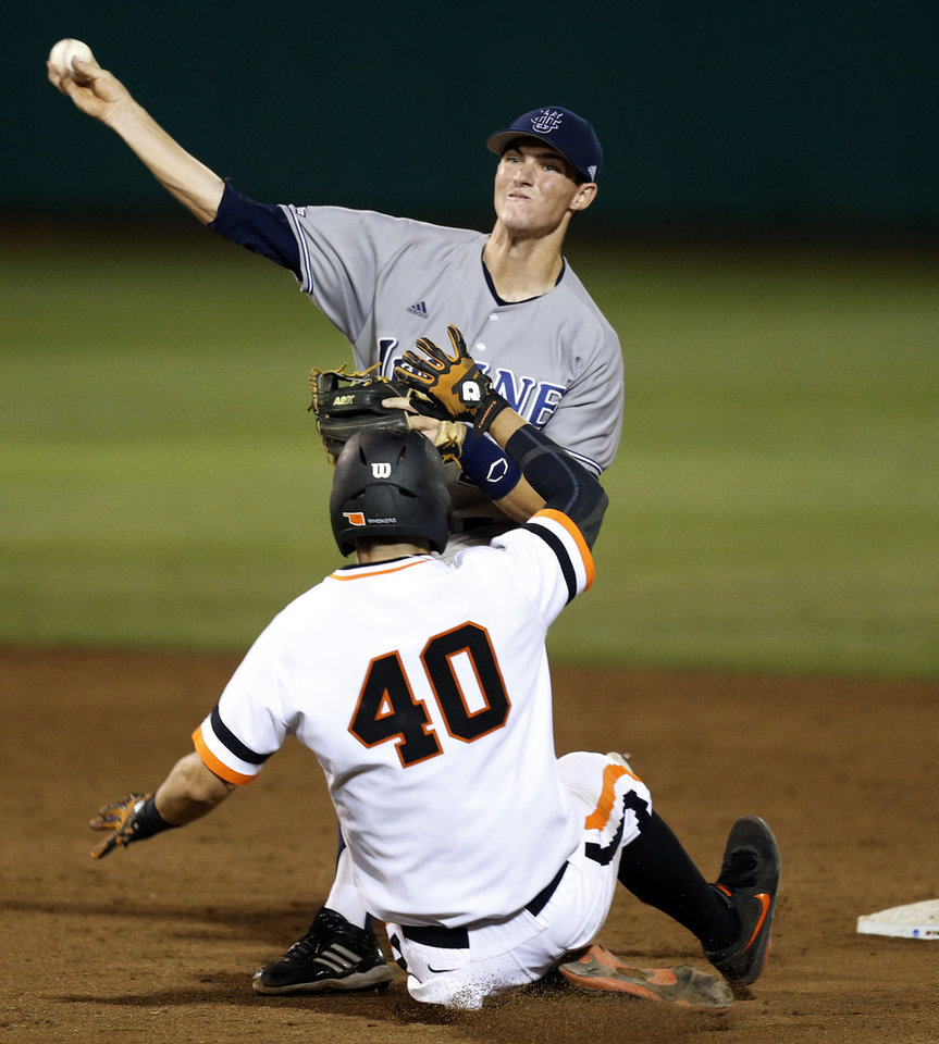 Photo - UC- rvine's John Brontsema (20) throws over OSU's Craig McConaughy (40) to complete a double play in the 8th inning during Game 1 of the NCAA baseball Stillwater Super Regional between Oklahoma State and UC Irvine at Allie P. Reynolds Stadium in Stillwater, Okla., Friday, June 6, 2014. Photo by Nate Billings, The Oklahoman