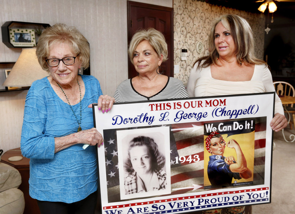 Photo -  Dorothy George and daughters Patsy Binkley and Sharee Herring, right, hold up a framed poster commemorating George's work at Douglas Aircraft during World War II. The poster is from George's 90th birthday party. [Photo by Jim Beckel, The Oklahoman]