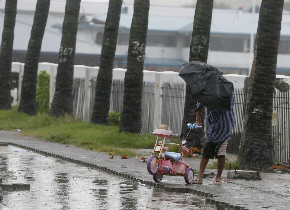 Photo - A man retrieves a baby tricycle under strong winds and slight rain brought by Typhoon Koppu Sunday, Oct. 18, 2015 in Manila, Philippines. The slow-moving typhoon blew ashore with fierce wind in the northeastern Philippines early Sunday, toppling trees and knocking out power and communications. Officials said there were no immediate reports of casualties. (AP Photo/Bullit Marquez)