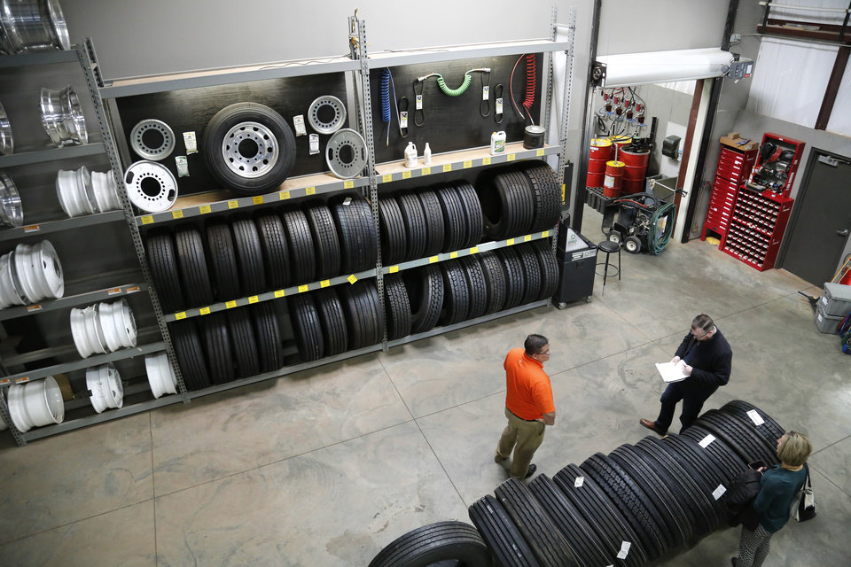 Photo -  Dan West, in orange, gives a tour of a tire repair center at one of the Guthrie Love's Travel Stops locations.
