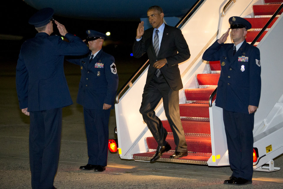 Photo - President Barack Obama salutes as he exits Air Force One as he returns to Andrews Air Force Base, Md., Thursday, July 17, 2014, after stops in Delaware and New York. (AP Photo/Jacquelyn Martin)