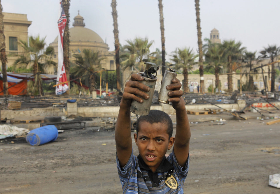 Photo - An Egyptian child displays empty tear gas canisters among the debris of a protest camp in Nahda Square, near Cairo University in Giza, Cairo, Egypt, Thursday, Aug. 15, 2013. Egypt faced a new phase of uncertainty on Thursday after the bloodiest day since its Arab Spring began, with over 300 people reported killed and thousands injured as police smashed two protest camps of supporters of the deposed Islamist president. Wednesday's raids touched off day-long street violence that prompted the military-backed interim leaders to impose a state of emergency and curfew, and drew widespread condemnation from the Muslim world and the West, including the United States. (AP Photo/Amr Nabil)