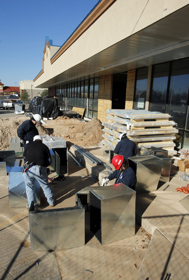 Photo - Metal workers construct air conditioning ducts last month at the site of a new Sprouts Farmers Market store on Main Street in Norman. Photo by STEVE SISNEY, THE OKLAHOMAN ARCHIVES