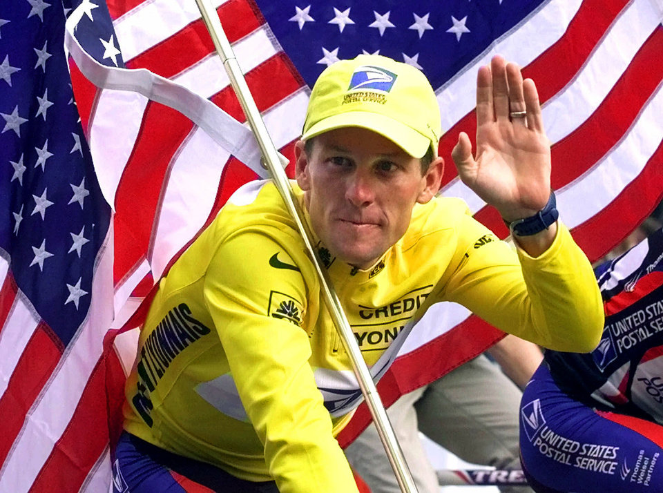 Photo - FILE - In this July 23, 2000, file photo, winner Lance Armstrong rides down the Champs Elysees after the final stage of the Tour de France cycling race in Paris. Armstrong also won the Prince of Asturias Award in Sports in 2000. Armstrong was stripped of his seven Tour de France titles and banned for life by cycling's governing body following a report from the U.S. Anti-Doping Agency that accused him of leading a massive doping program on his teams. (AP Photo/Laurent Rebours, File)