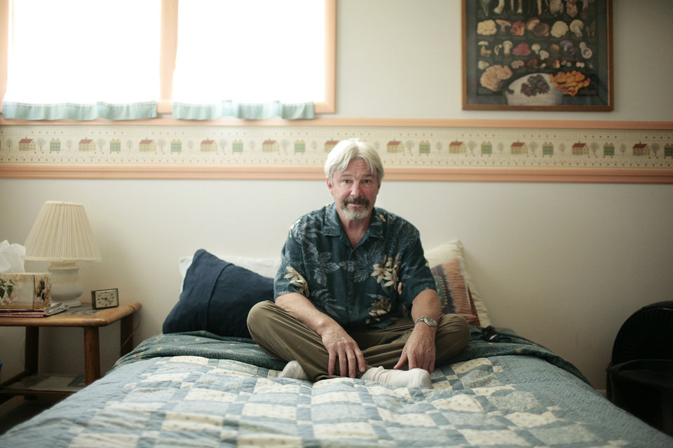 FILE - In this July 22, 2011 photo, Don Killian sits on the bed he offers up to strangers at no cost in Bozeman, Mont. Killian is one of the 150 Bozeman, Mont.,members of CouchSurfing.org, a website for travelers looking for a free place to stay. (AP Photo/Bozeman Daily Chronicle, Nick Wolcott)
