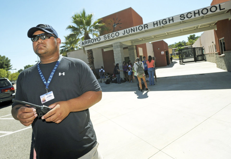Photo -   Campus supervisor Jerome Castaneda monitors the parking lot following dismissal at Arroyo Seco Junior High School in the Valencia neighborhood of Santa Clarita, Calif., Tuesday, Sept. 18, 2012. Eric Yee, accused of posting comments on ESPN's website saying he was watching kids and wouldn't mind killing them, was in jail Tuesday on $1 million bail after he was arrested at his home near the school for investigation of making terrorist threats, authorities said. (AP Photo/Santa Clarita Valley Signal, Jonathan Pobre) MANDATORY CREDIT