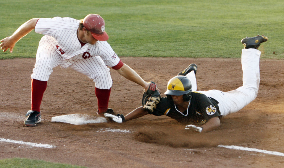 Photo - First Baseman Aaron Baker tags Will Baez out after a throw from the catcher as the University of Oklahoma plays Wichita State at L. Dale Mitchell Park in the NCAA Regional baseball tournament in Norman, Okla. on Friday, May 29, 2009. 