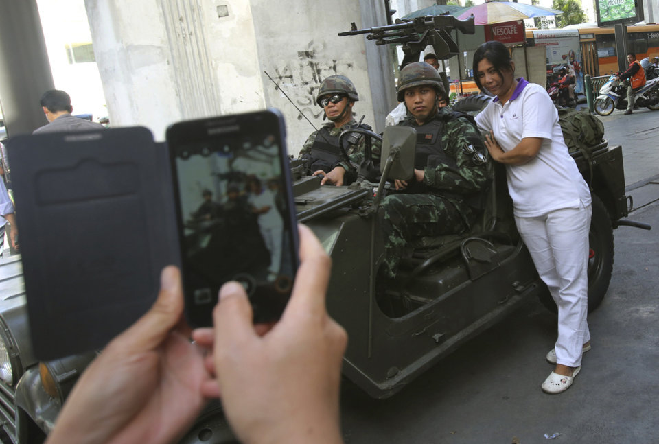 Photo - A Thai woman take pictures with Thai soldiers stationed outside the Thai police headquarters Tuesday, May 20, 2014, in Bangkok, Thailand. Thailand's army declared martial law before dawn Tuesday in a surprise announcement it said was aimed at keeping the country stable after six months of sometimes violent political unrest. The military, however, denied a coup d'etat was underway. (AP Photo/Sakchai Lalit)