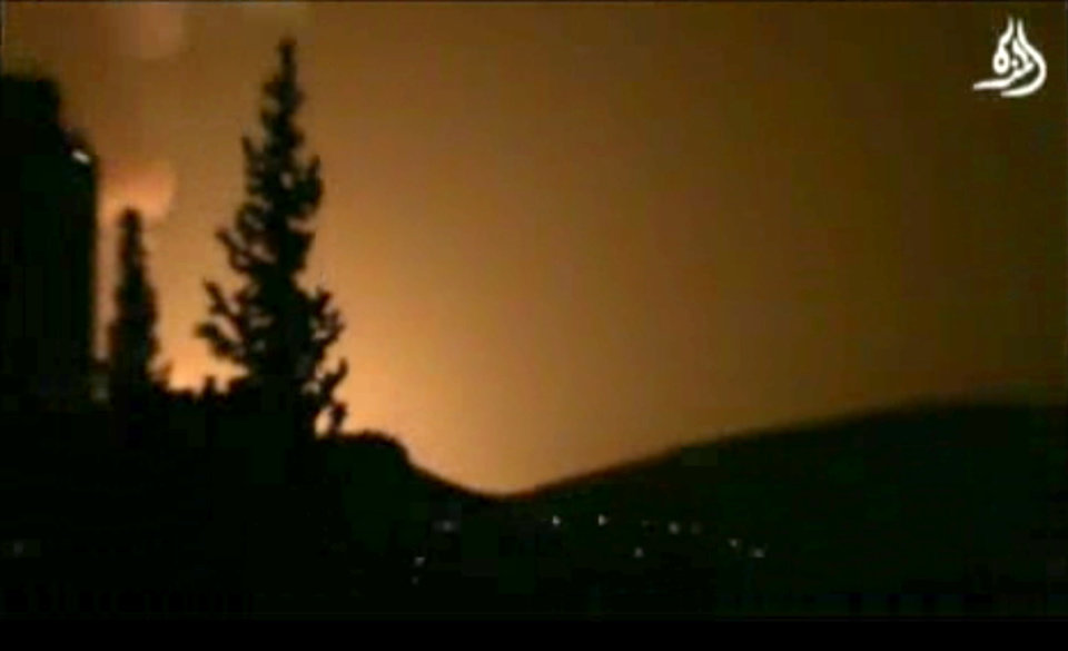Photo - In this image taken from video obtained from Shaam News Network, which has been authenticated based on its contents and other AP reporting, smoke and fire fill the skyline over Damascus, Syria, early Sunday, May 5, 2013 after an Israeli airstrike. Israeli warplanes struck areas in and around the Syrian capital Sunday, setting off a series of explosions as they targeted a shipment of highly accurate, Iranian-made guided missiles believed to be on their way to Lebanon's Hezbollah militant group, officials and activists said. The attack, the second in three days, signaled a sharp escalation of Israel's involvement in Syria's bloody civil war. Syria's state media reported that Israeli missiles struck a military and scientific research center near the Syrian capital and caused casualties. (AP Photo/Shaam News Network via AP video)