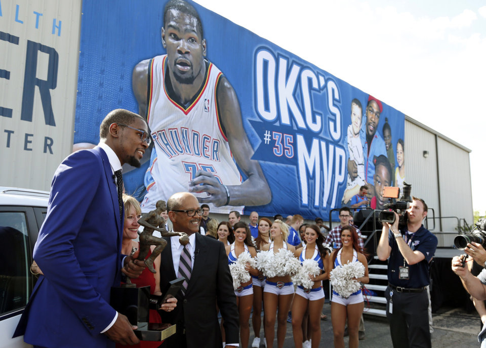 Photo - Oklahoma City Thunder forward Kevin Durant, left, poses for a photo with Lisa Williams, center, executive director of Moore Youth and Family Services, and Percy Vaughn, right, of Kia, following the announcement of Durant as the winner of the 2013-14 Kia NBA Basketball Most Value Player Award in Oklahoma City, Tuesday, May 6, 2014. As the winner, Durant receives a Kia, which he is donating to the charity. (AP Photo/Sue Ogrocki)