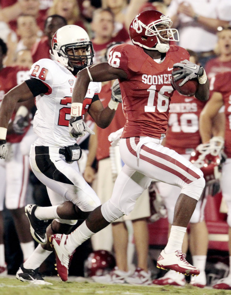Photo - Oklahoma Sooners' Jaz Reynolds (16) runs near the goal line pursued by Andre Dawson (28) during the first half of the college football game between the University of Oklahoma Sooners (OU) and the Ball State Cardinals at Gaylord Family-Oklahoma Memorial Stadium on Saturday, Oct. 1, 2011, in Norman, Okla. Photo by Steve Sisney, The Oklahoman