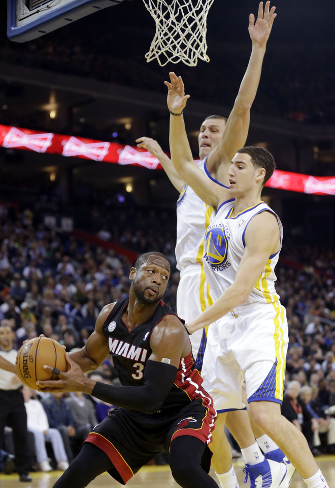 Miami Heat's Dwyane Wade (3) is defended by Golden State Warriors' Klay Thompson (11) and Andris Biedrins, center, during the first half of an NBA basketball game in Oakland, Calif., Wednesday, Jan. 16, 2013. (AP Photo/Marcio Jose Sanchez)
