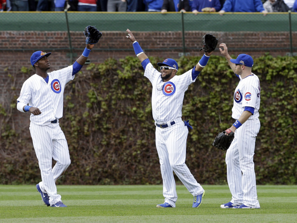 Photo - Chicago Cubs center fielder Emilio Bonifacio, center, celebrates with left fielder Junior Lake, left, and right fielder Nate Schierholtz after the Cubs defeated the Milwaukee Brewers 3-0 in a baseball game in Chicago, Saturday, May 17, 2014. (AP Photo/Nam Y. Huh)