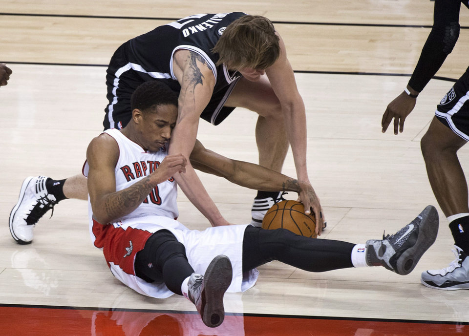 Photo - Toronto Raptors guard DeMar DeRozan (10) vies for the ball against Brooklyn Nets forward Andrei Kirilenko during the first half of Game 2 in an NBA basketball first-round playoff series, Tuesday, April 22, 2014, in Toronto. (AP Photo/The Canadian Press, Nathan Denette)