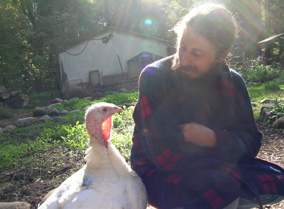 This undated photo provided by Love Creek Farm shows a pet turkey, Ariala, and her owner, Mike Balistreri, spending quality time together in the garden at Love Creek Farm in Ben Lomond, Calif. (AP Photo/Love Creek Farm)