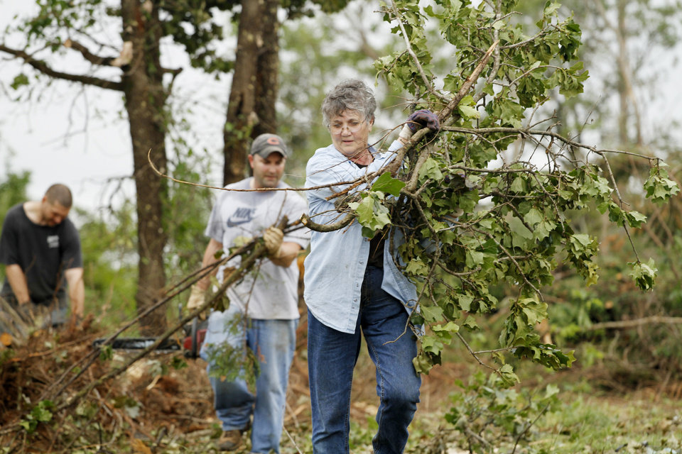 Pat Ward carries branches to the street that Rory Farmer, background left, and Dustin Moss have cut up with their chain saws in the Dripping Springs Estates Saturday, May 15, 2010. Saturday hundreds of volunteers went into areas that had been affected by last week's tornadoes to help clear debris. Photo by Doug Hoke, The Oklahoman.