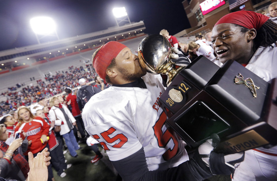 Carl Albert's Kyler Weaver (55) and Bryan Williams (55) celebrate with the trophy during the Class 5A Oklahoma state championship football game between Carl Albert High School and Tulsa East Central High School at Boone Pickens Stadium on Saturday, Dec. 1, 2012, in Stillwater, Okla.   Photo by Chris Landsberger, The Oklahoman