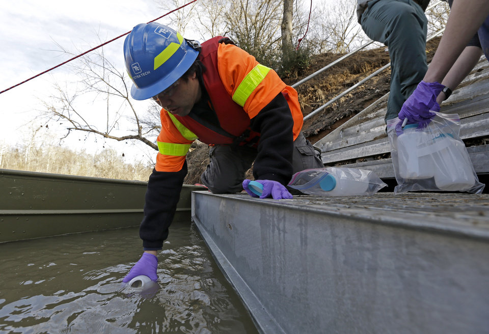 Photo - Didi Fung, a contractor for the Environmental Protection Agency, collects water samples from the Dan River as state and federal environmental officials continued their investigations of a spill of coal ash into the Dan River in Eden, N.C., Wednesday, Feb. 5, 2014. Duke Energy estimates that up to 82,000 tons of ash has been released from a break in a 48-inch storm water pipe at the Dan River Power Plant on Sunday. (AP Photo/Gerry Broome)