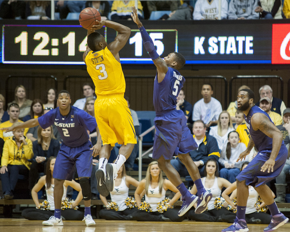 Photo - West Virginia's Juwan Staten, left, shoots over Kansas State's Jevon Thomas during the first half of an NCAA college basketball game Saturday, Feb. 1, 2014, in Morgantown, W.Va. (AP Photo/Andrew Ferguson)