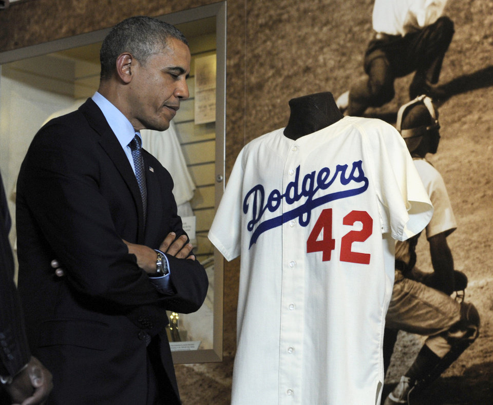 Photo - President Barack Obama looks at Jackie Robinson's Brooklyn Dodgers baseball jersey during a tour the Baseball Hall of Fame in Cooperstown, N.Y., Thursday, May 22, 2014. Obama visited the museum to highlight tourism and steps to help spur international visits to the 50 states. Obama said the overall U.S. economy and local businesses will benefit if it isn't a hassle for people from other countries to visit the U.S. and spend money at its hotels, restaurants, tourist destinations and other businesses. (AP Photo/Susan Walsh)