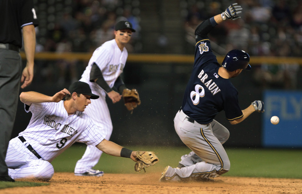 Photo - Milwaukee Brewers' Ryan Braun (8) steals second base as the ball goes past Colorado Rockies second baseman DJ LaMahieu (9) in the ninth inning of a baseball game in Denver on Friday, June 20, 2014. Rockies shortstop Troy Tulowitzki backs up the play.(AP Photo/Joe Mahoney)