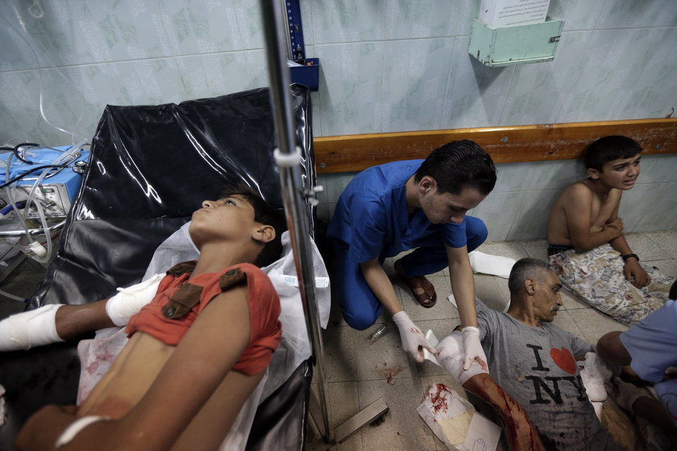 Photo - Palestinians who were wounded in an Israeli strike on a house in Beit Lahiya lie on the floor at they are treated at the emergency room of the Kamal Adwan Hospital, in Beit Lahiya,  northern Gaza Strip, Sunday, Aug. 3, 2014. (AP Photo/Lefteris Pitarakis)
