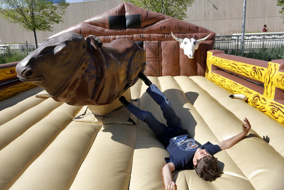 Photo - Mason Roberts is thrown from the mechanical bull while enjoying Thunder Alley before the start of Game 2 in the first round of the NBA playoffs between the Oklahoma City Thunder and the Houston Rockets at Chesapeake Energy Arena in Oklahoma City, Wednesday, April 24, 2013. Photo by Chris Landsberger, The Oklahoman