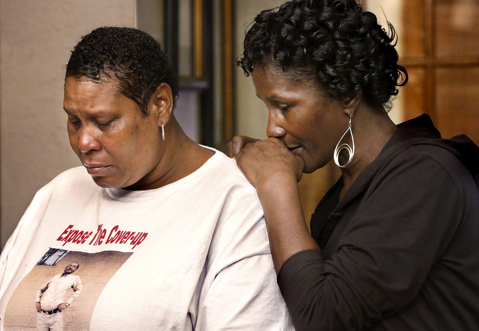 Photo - Tears form in the eyes of Deidra Hill, left, Robin Leander Howard's sister, as she and Cynthia Hill, his sister-in-law, listen during a news conference Wednesday in attorney David Slane's office. PHOTO BY JIM BECKEL, THE OKLAHOMAN