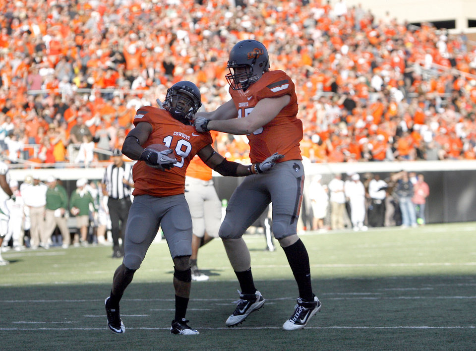 Photo - Oklahoma State's Brodrick Brown (19) and Caleb Lavey (45) celebrate an interception during a college football game between the Oklahoma State University Cowboys (OSU) and the Baylor University Bears (BU) at Boone Pickens Stadium in Stillwater, Okla., Saturday, Oct. 29, 2011. Photo by Sarah Phipps, The Oklahoman