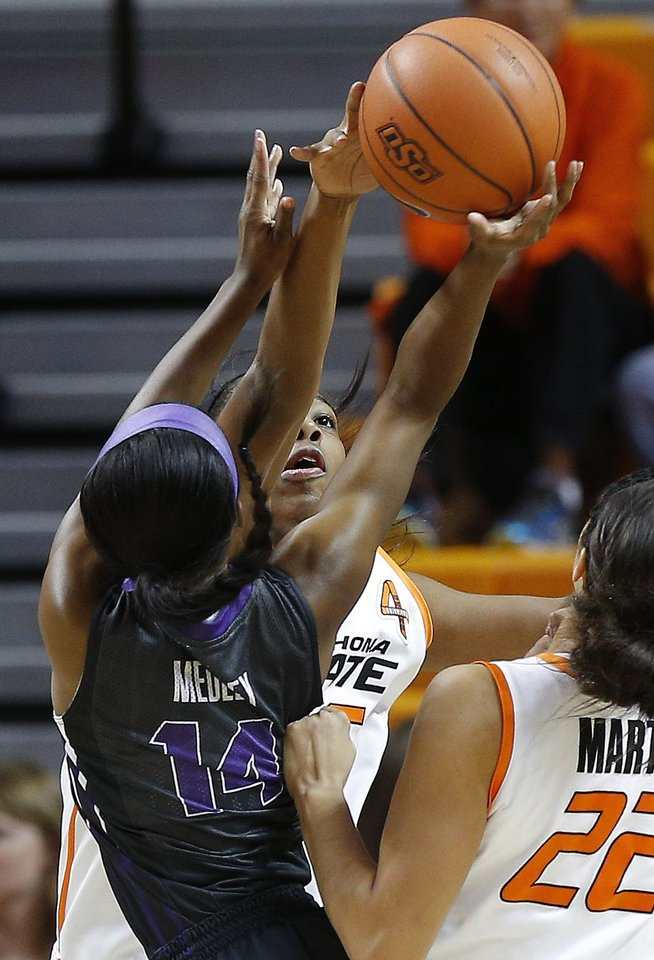 Oklahoma State\'s LaShawn Jones (55) blocks the shot of TCU\'s Zahna Medley (14) during a women\'s NCAA college basketball game between Oklahoma State University (OSU) and TCU at Gallagher-Iba Arena in Stillwater, Okla., Tuesday, Jan. 14, 2014. Photo by Bryan Terry, The Oklahoman