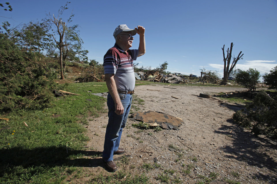 Photo - A.J. Pearcy surveys his new skyline with deleted barns, and trees as residents cleanup following Tuesday's deadly tornado  on Wednesday, May 25, 2011, in Chickasha, Okla. Photo by Steve Sisney, The Oklahoman
