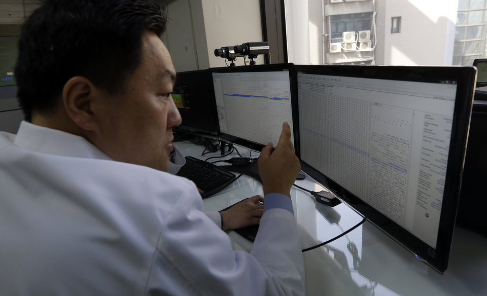 Photo - A South Korean computer researcher looks at a computer monitor as he checks the shutdown computer servers of Korean Broadcasting System (KBS) at Evidence Acquisition Lab of Cyber Terror Response Center at National Police Agency in Seoul, South Korea, Thursday, March 21, 2013. A Chinese Internet address was the source of a cyberattack on one company hit in a massive network shutdown that affected 32,000 computers at six banks and media companies in South Korea, initial findings indicated Thursday. (AP Photo/Lee Jin-man)