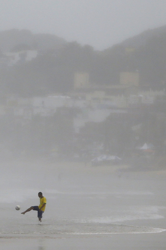 Photo - Arthur Gomes Freire, 28, kicks a ball during a rainy day at the beach in Natal, Brazil, Saturday, June 14, 2014. Natal is one of 12 cities hosting games during the 2014 World Cup soccer tournament. (AP Photo/Julio Cortez)