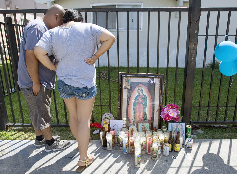 A couple who didn't want to be identified look at the memorial set up for Manuel Diaz, 25, who was killed in an officer-involved shooting in Anaheim, Calif., Sunday July 22, 2012. The incident sparked a Saturday night melee and Sunday protests. (AP Photo/The Orange County Register, Mindy Schauer) MAGS OUT; LOS ANGELES TIMES OUT MANDATORY CREDIT, MINDY SCHAUER, THE ORANGE COUNTY REGISTER.