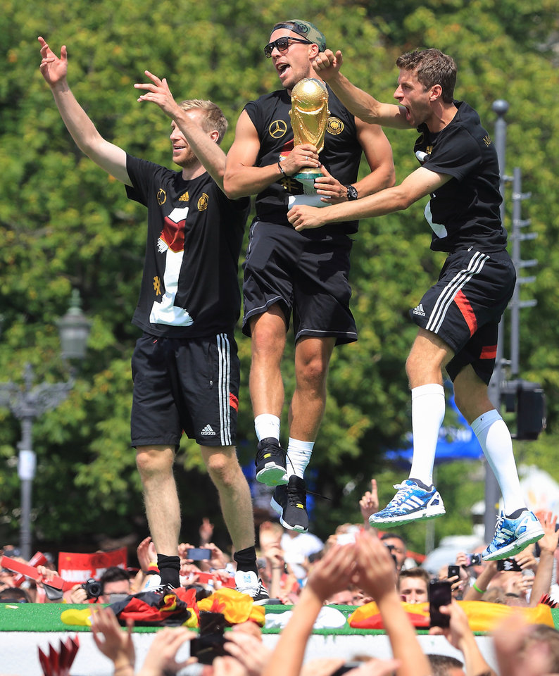 Photo - German national soccer players from left: Per Mertesacker , Lukas Podolski and Thomas Mueller celebrate near Brandenburg Gate in Berlin, Tuesday July 15, 2014.    Germany's World Cup winners shared their fourth title with hundreds of thousands of fans by parading the trophy through cheering throngs to celebrate at the Brandenburg Gate on Tuesday. An estimated 400,000 people packed the