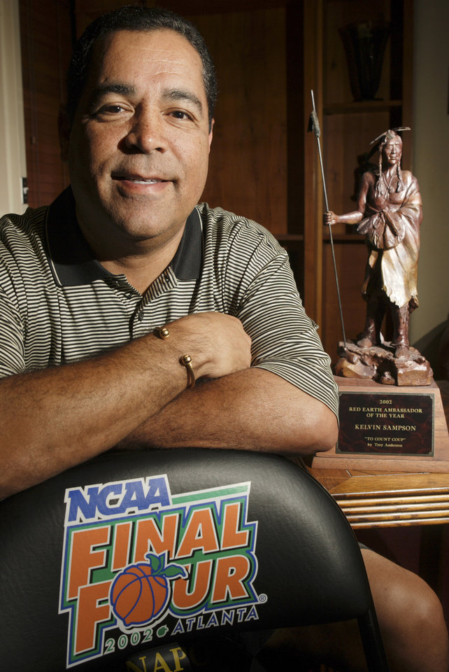 Photo - Kelvin Sampson, head basketball coach, University of Oklahoma (OU), poses in his office with a chair from his visit to the 2002 Final Four and the 2002 Red Earth Ambassador of the Year award he received. The award is a statue titled