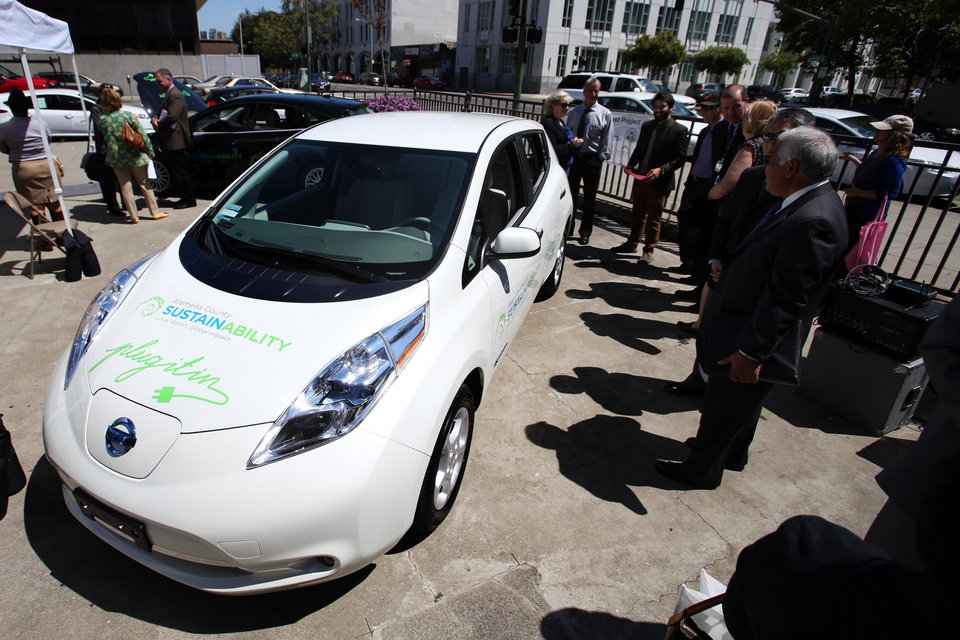 Photo - Bay Area city officials look at new electric vehicles during a press conference at the AlcoPark Garage Plaza in Oakland, Calif., Tuesday, July 8, 2014. A group of San Francisco Bay Area cities, counties and water agencies has joined forces for what is being billed as one of the largest single government purchases of all-electric vehicles in the country. (AP Photo/Bay Area News Group, Ray Chavez)