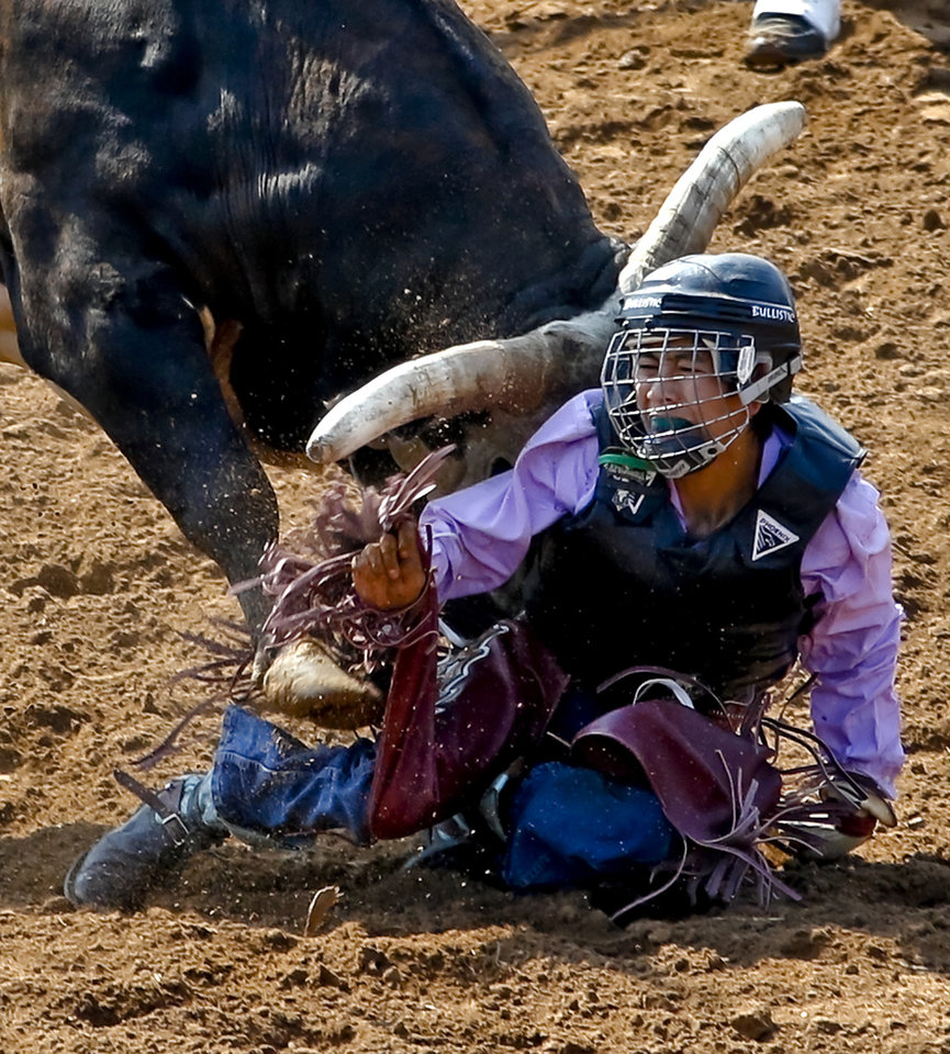 Clay Wagner, of Ariz., is hit by the bull after being thrown off during day three of the International Finals Youth Rodeo at the Shawnee Expo Center in Shawnee, Okla. Tuesday, July 10, 2012.   Photo by Chris Landsberger, The Oklahoman